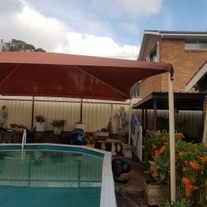 Hip and ridge shade structure over a residential pool